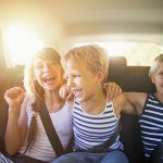 Three kids laughing in car on a road trip. Kids are aged 10 and 7. The kids are laughing and embracing, Sunny summer day.