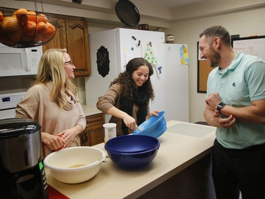 Tessa laughs with Family-Teachers Jaclyn and Andrew as they cook dinner at their home. (Photo: Zach Boyden-Holmes/The Register)