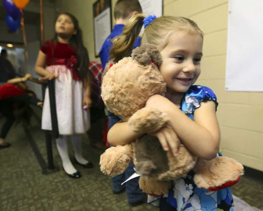 Izabellah Allen hugs a stuffed toy she received at the Boys Town Texas offices before the Reunification Recognition Celebration.