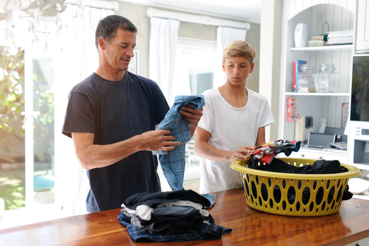 Father and son folding laundry