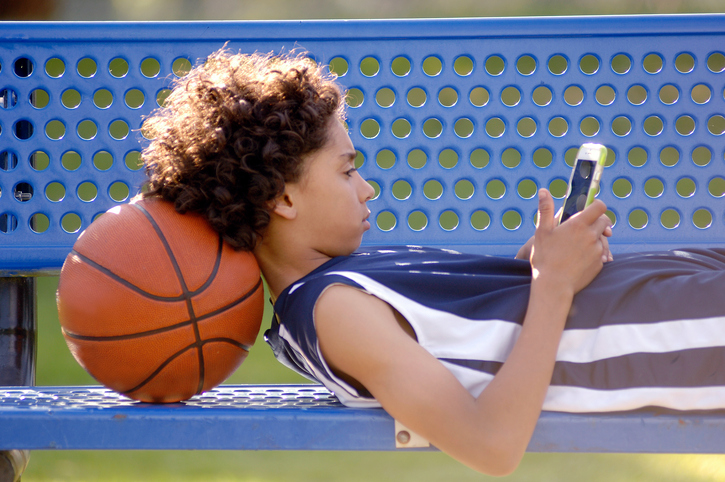 Boy laying on a bench, looking at a cell phone