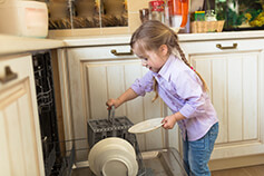 Child putting dishes in dish washer