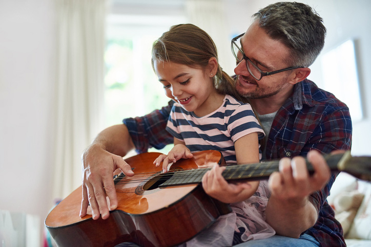 Dad teaching daughter to play guitar