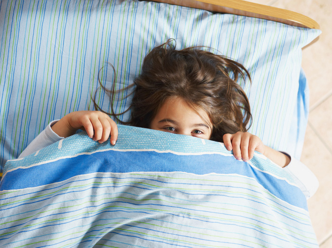 Child in bed with covers up to her nose