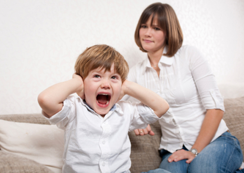 Child screaming and covering his ears
