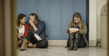 Teen sitting against lockers, alone