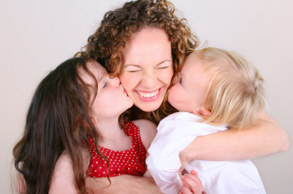 Daughters kissing Mom on the cheek