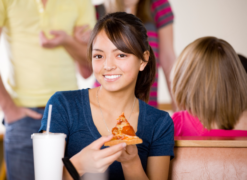 Teen eating pizza