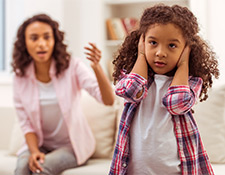 Daughter with hands over her ears, ignoring parent